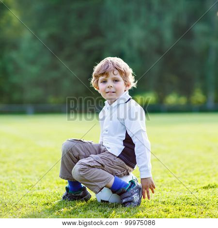 Blond Boy Of 4 Resting With Football On Football Field