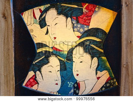 Fragment of the antique lamp. Japanese colorful female faces on the canvas