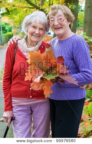 Happy Middle Age Women Holding Autumn Leaves.