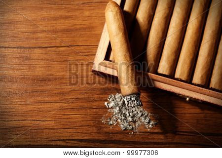 Cigars and burnt one with ash on wooden table, top view