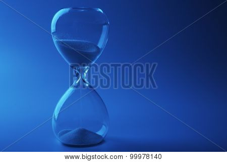 Hourglass on color background