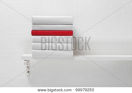 Blank books and red one on shelf on white wallpaper background