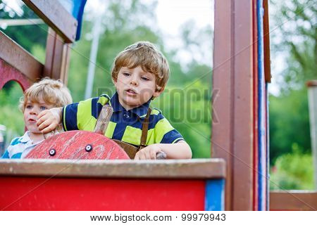 Two Kid Boys Pretends Driving An Imaginary Car On Playground,