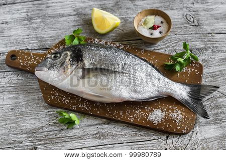Fresh Dorado Fish With Lemon And Spices On A Light Wooden Surface