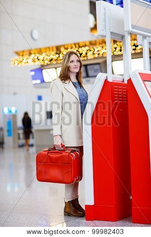 Woman At International Airport, Checking In On Electronic Termin