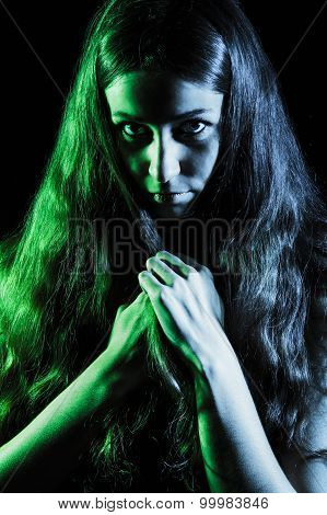 Scary Face Of A Young Woman In Green And Grey Lights