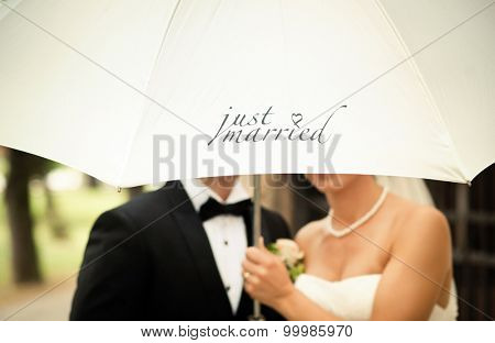 Just married couple holding white umbrella with text