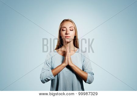 Closeup Portrait Of A Young Blonde Woman Praying With Closed Eyes Isolated On Blue Background