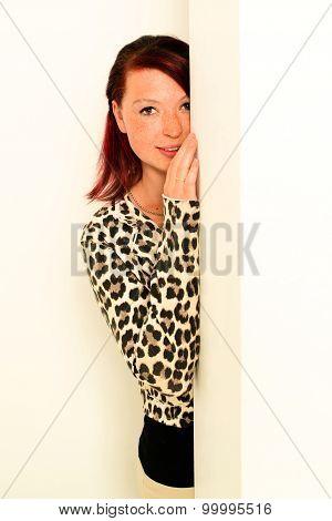 young woman peeking around the wall