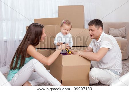 Cheerful young married couple and their child are moving