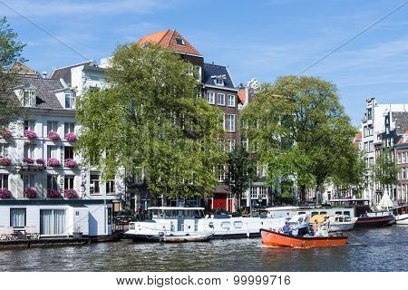 Small Boat With Relaxing People In Amsterdam Canal