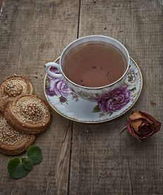 stock photo of english rose  - Cup of english tea homemade bakery puff cookies with sesame seeds on plate and dry rose - JPG